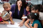 A head and shoulders image of a teacher in a classroom teaching a group of small children in school. Zoya Vincent, Soleil, Brianne Burke, Salem Neufeld, Lluvia Quintana